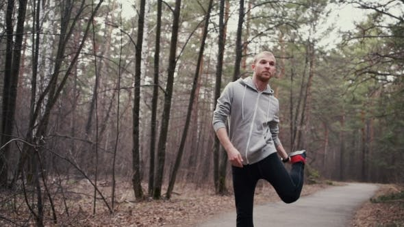 Man Running In Forest Woods Training And Look At Smart Watch