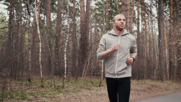 Thumbnail for Man Running In Forest Woods Training And Look At Smart Watch