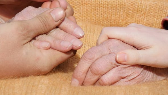 Cover Image for A Young Male And Female Hands Comforting a Old Pair Of Hands Outdoor.