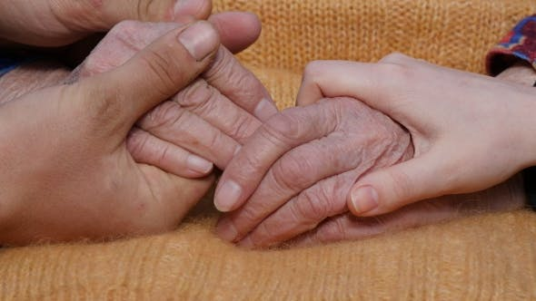 Thumbnail for A Young Man's And Woman's Hands Comforting a Old Pair Of Hands Of Grandmother Outdoor.