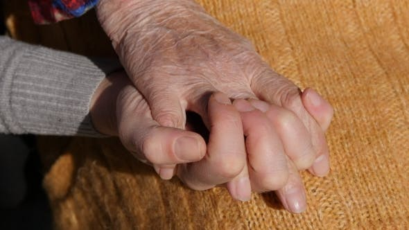 Thumbnail for A Young Female Hands Comforting An Elderly Pair Of Hands Of Grandma Outdoor .