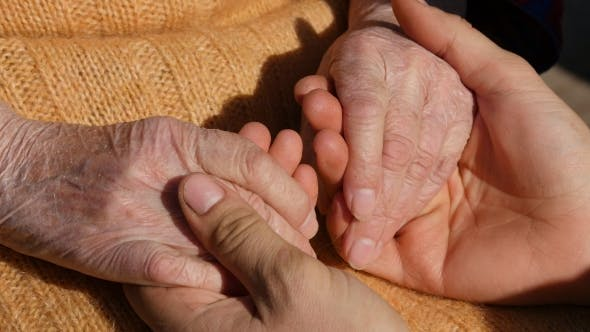 Thumbnail for A Young Male Hands Comforting an Elderly Pair of Hands of Grandma Outdoor