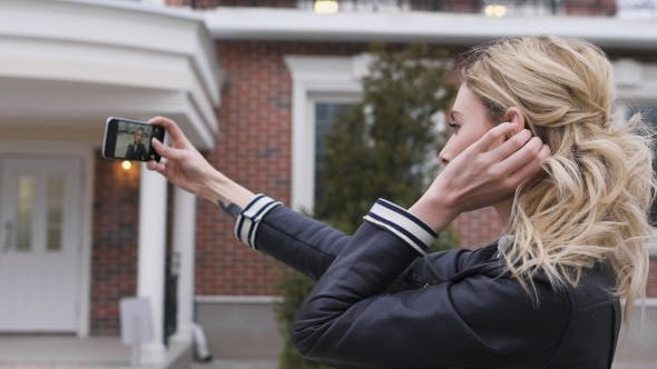 Thumbnail for Side Portrait Of a Beautiful Blond Girl Using a Smart Phone To Take Selfies