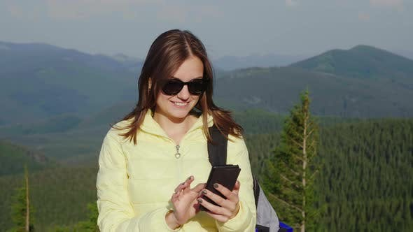 Thumbnail for Portrait of Young Woman Enjoying a Smartphone on a Picturesque Backdrop of Mountains Covered with