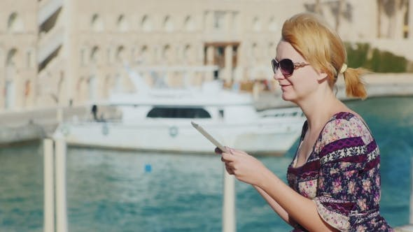 Thumbnail for Young Woman Enjoying a Tablet Against The Background Of The Bay With Yachts