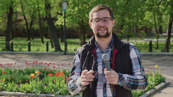 Thumbnail for Male Reporter With a Microphone Tells News Camera. It Should Be In The Spring Park On a Background