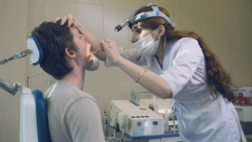Otolaryngologist Checking Man in Consulting Room