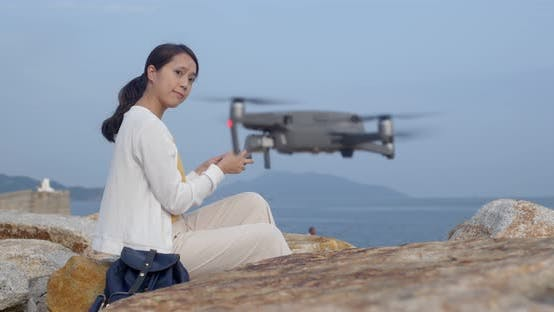 Thumbnail for Woman fly a drone and stand at the sea side