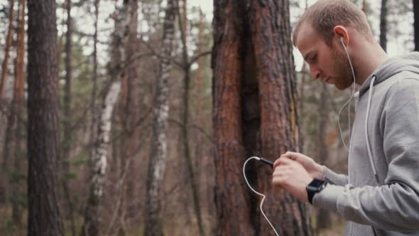 Thumbnail for Young Handsome Runner With Smart Phone Outside In Sunny Autumn Nature.