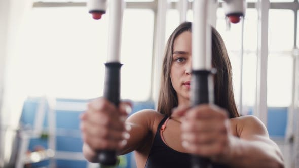 Thumbnail for Young Woman Flexing Muscles On Cable Gym Machine