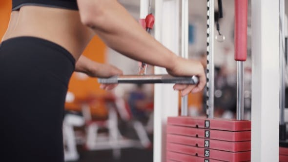 Cover Image for Young Woman Flexing Muscles On Cable Gym Machine
