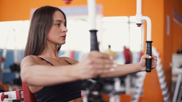 Cover Image for Young Woman Flexing Muscles On Cable Gym Machine.