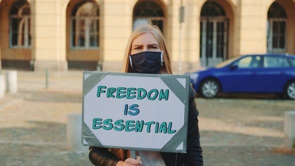 Woman in Mask on Protest Walk Calling That Freedom Is Essential
