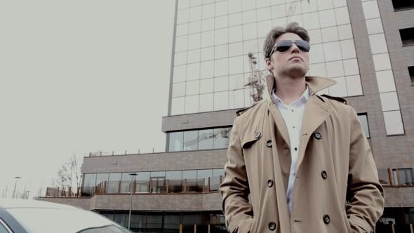 A Man In a Coat And Sunglasses