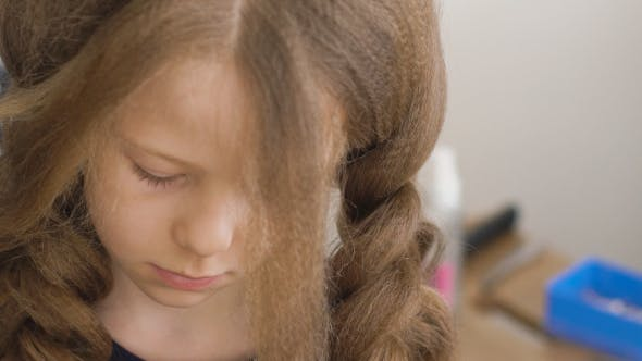 Thumbnail for Unhappy Little Girl. Mom or Barber Braids Her Braids. Brown Hair