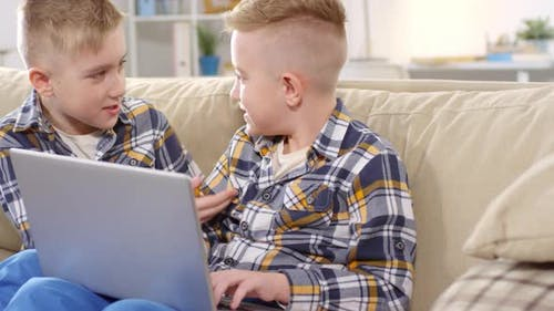 Agitated Caucasian Twins Typing on Laptop