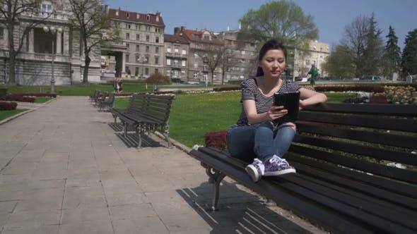 Thumbnail for Asian Girl Working With a Tablet Pc In a Green Park