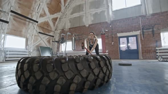 Thumbnail for Woman Doing Sledgehammer Exercise with Tire