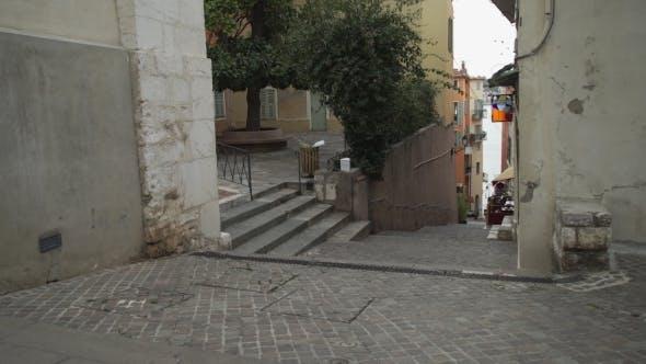 Thumbnail for Woman Walking Narrow Street Holding Laptop.