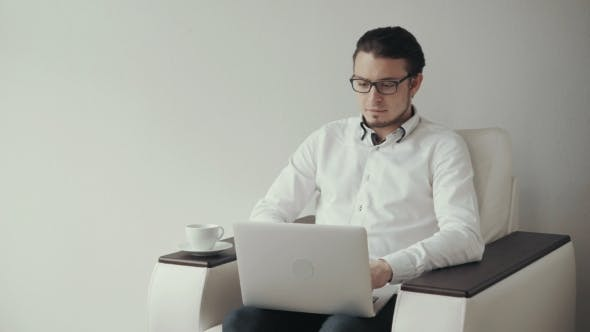 Thumbnail for Young Man in Glasses Sitting in Arm Chair and Using Laptop. White Background.
