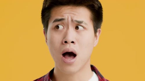 Portrait Of Shocked Asian Man Posing Standing On Yellow Background