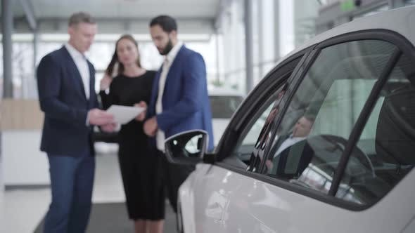 Thumbnail for Blurred Car Dealer Showing Booklet To Multiracial Couple in Showroom. Young Middle Eastern Man and
