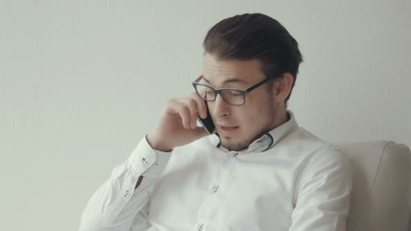 Thumbnail for Portrait Of Young Man In Glasses Talking On The Phone Against White Background