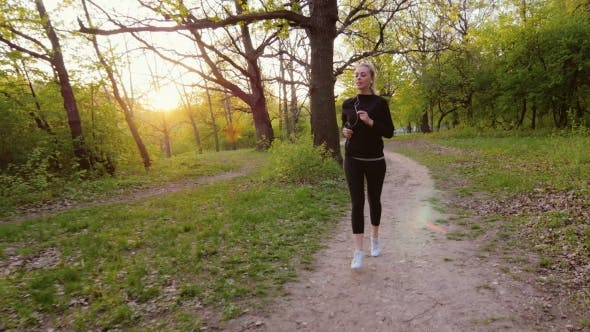 Thumbnail for Jogging In Spring Forest. Woman Running In The Forest, The Sun Is Shining It In The Back
