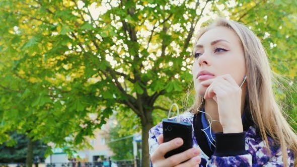 Thumbnail for Attractive Woman Listening To Music In The Park. She Headphones, Spring Outdoors