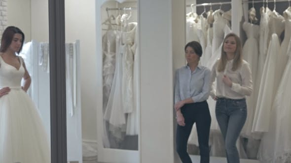 Thumbnail for Beautiful Bride At The Clothes Shop For Wedding Dresses, She Is Choosing a Dress With Bridesmaids