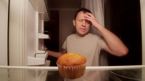 Refrigerator of a lonely young man, one spoiled cupcake on the shelf