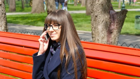 Thumbnail for Young Woman In Glasses Talking On The Modile Phone In a City Park. Girl Sitting On a Red Bench