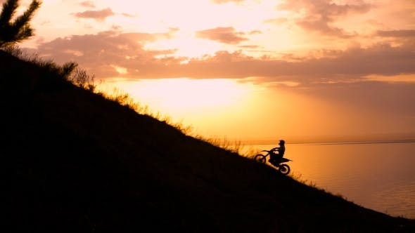 Motocross Bike At Sunset On Hill Climbs.