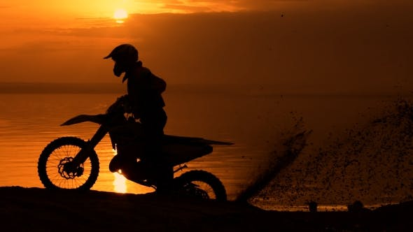 Thumbnail for Off-road Motorbike Extreme Cornering. Motorcyclist At Sunset Near The River. Extreme Motocross Bike