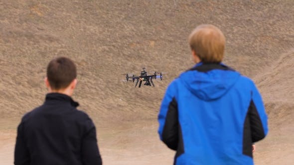 Thumbnail for Two Engineers Watching The Drone Landing. Quadrocopters Sits In Automatic Mode,