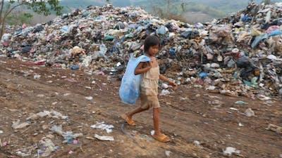 Poverty Kid Walking With Garbage Bag