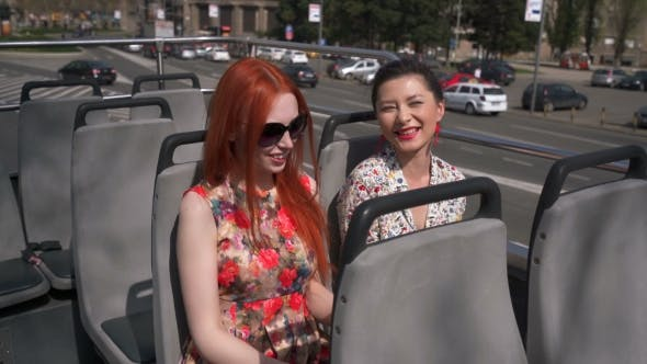 Thumbnail for Young Sexy Women Listening Audiotape On An Open Top Bus