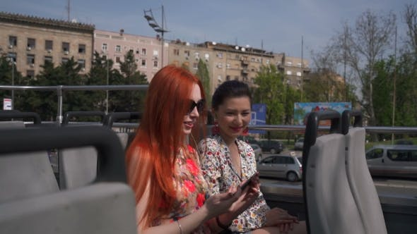 Thumbnail for Two Young Pretty Women Taking Selfie On An Open Top Bus