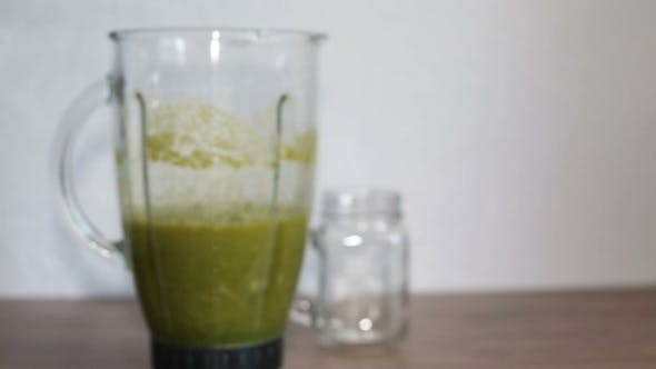 Thumbnail for A Blender Jar With Green Healthy Smoothie And a Mason Jar On a Wooden Table