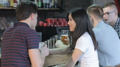Three Men With a Girl Drink Alcoholic Drinks At The Bar