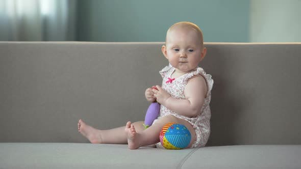 Baby Smiling and Playing With Toys on Sofa, Infant Enjoying Comfort in Diapers