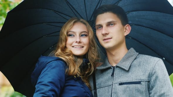 Thumbnail for Young Beautiful Couple Standing Under An Umbrella