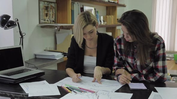Thumbnail for Two Girls Examine And Discussing Some Charts Sitting At a Desk In The Office