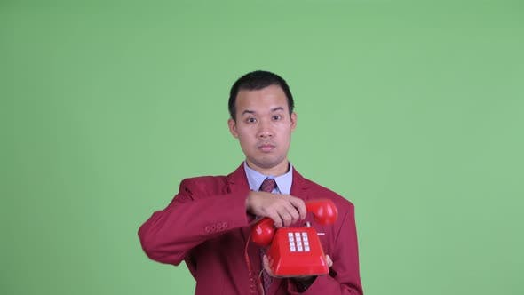 Thumbnail for Face of Happy Asian Businessman Using Telephone and Looking Surprised