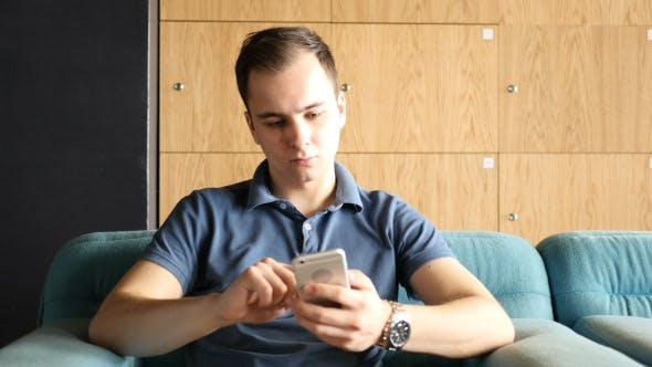 Thumbnail for Young Man Using Smartphone while Sitting on Sofa