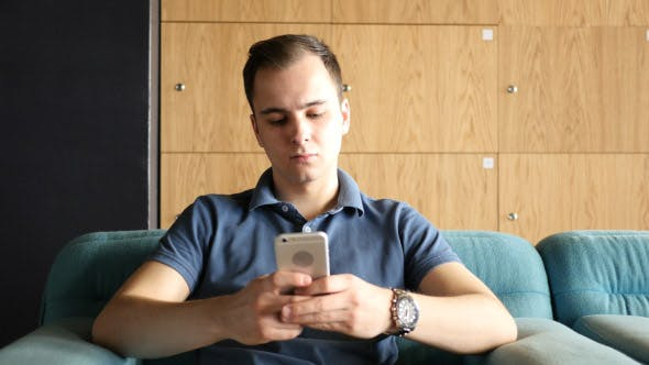 Thumbnail for Man Texting on Smartphone while Sitting on Sofa