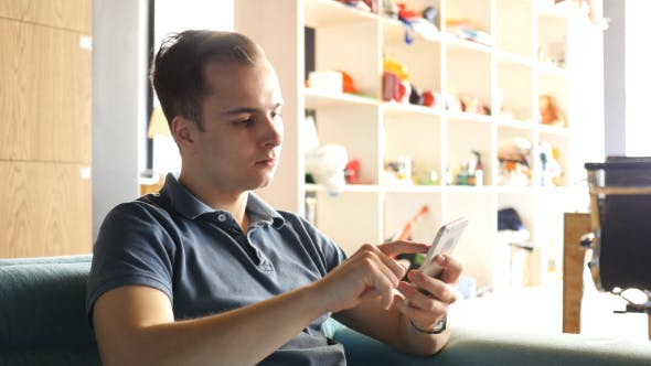 Thumbnail for Man Using Smartphone while Sitting on Sofa
