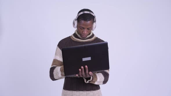 Cover Image for Young Happy African Man Using Laptop Ready for Winter