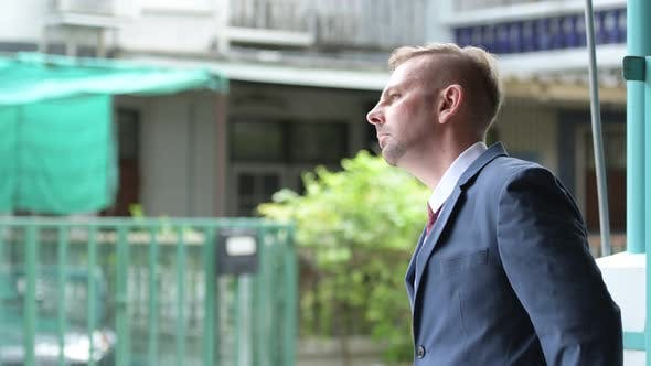 Thumbnail for Profile View of Blonde Businessman Waiting Outdoors