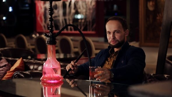 Cover Image for Young Intelligent Man Smoking Hookah